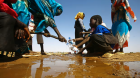 A Sudanese woman fills water bottles held by a young boy in North Darfur state. Within two decades 600 million children will be in regions enduring extreme water stress. Photograph: Ashraf Shazly/AFP/Getty Images